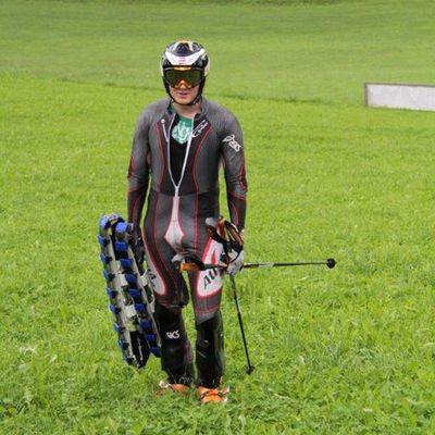 Mann mit Grasskiausrüstung: Ski, Helm, Stecken